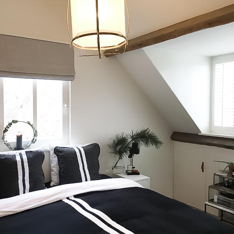 slaapkamer zwart beddengoed houten balken wit en licht