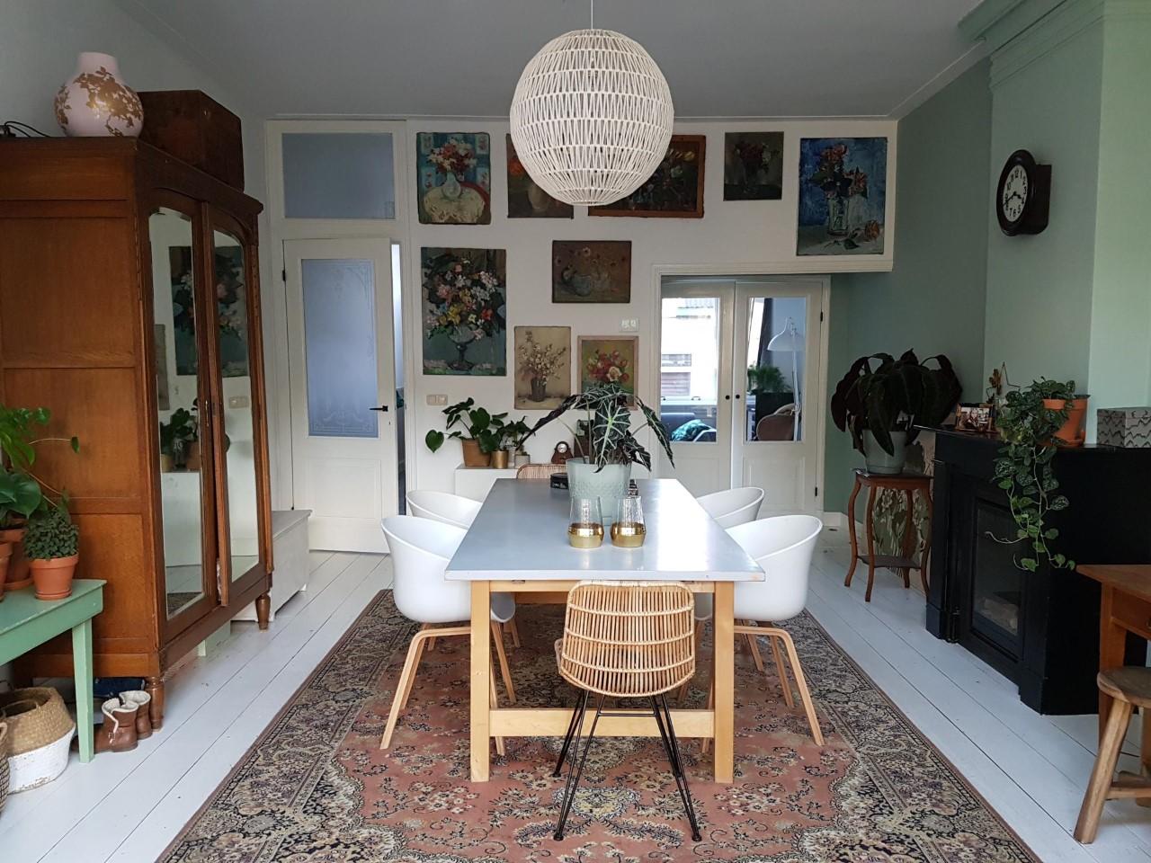 eclectische olieverf schilderijen en kamerplanten in witte woonkeuken