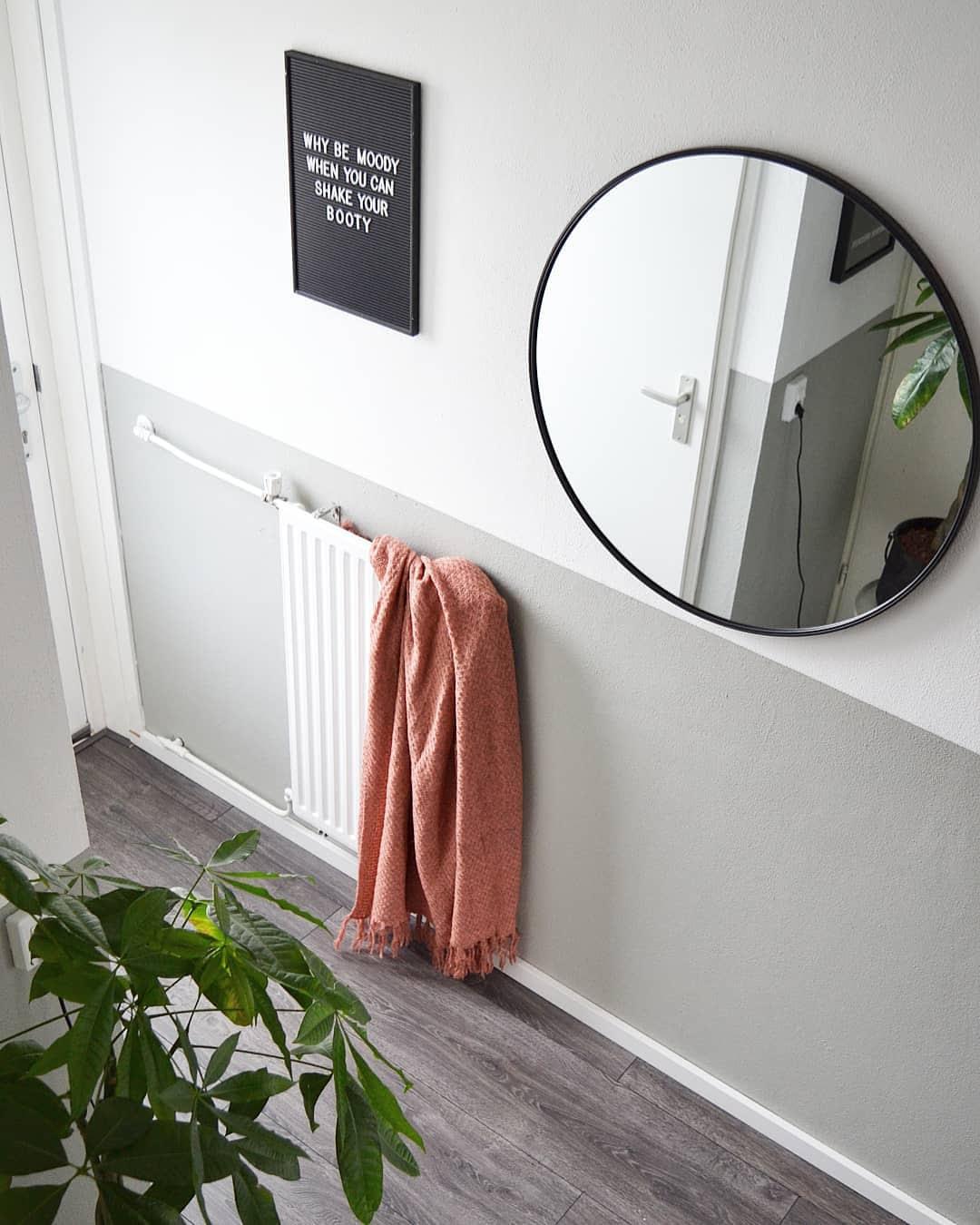 ronde spiegel in lichte hal met letterbord en plant
