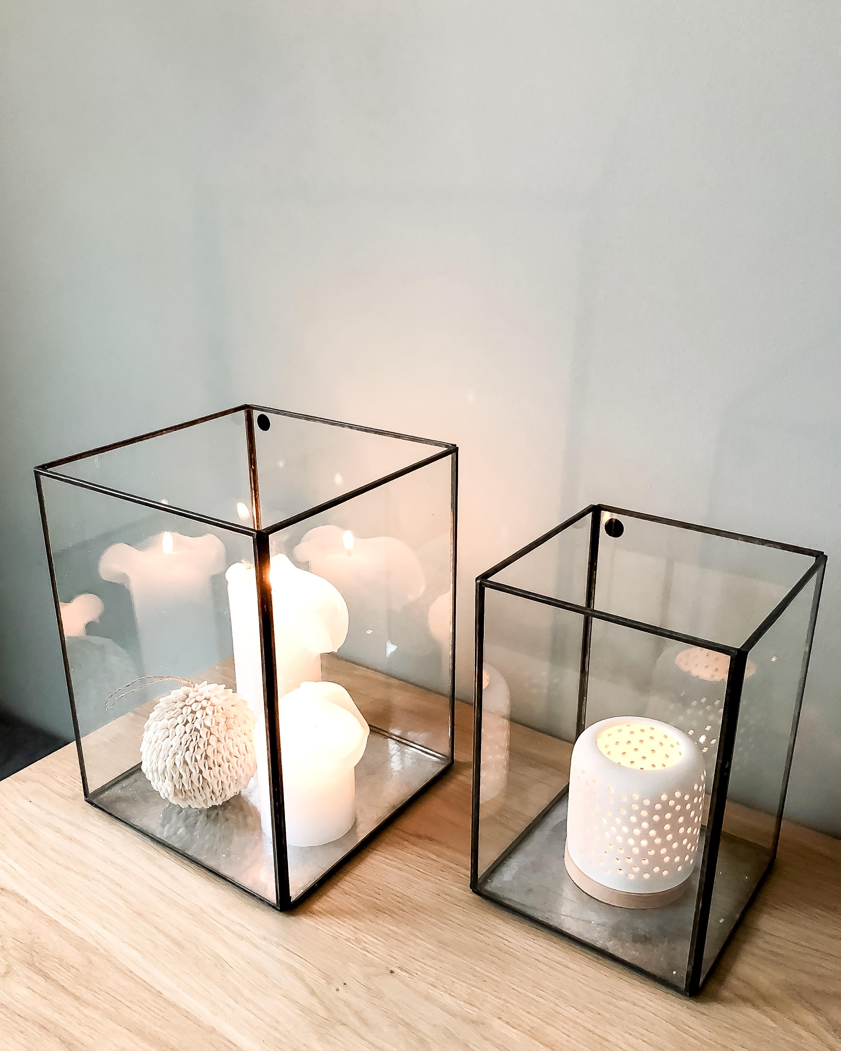 kaarsen in glazen box op wandmeubel